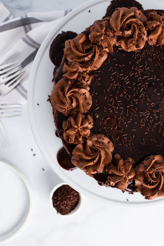 hot fudge brownie cheesecake garnished with chocolate sauce and chocolate whipped cream swirls on a white cake pedestal