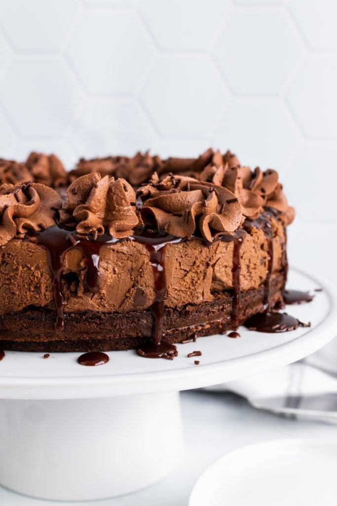 hot fudge brownie cheesecake on a white cake pedestal