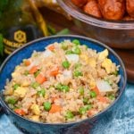 a bowl shown full of this copy cat fried rice with a bottle of soy sauce and a bowl of orange chicken in the background