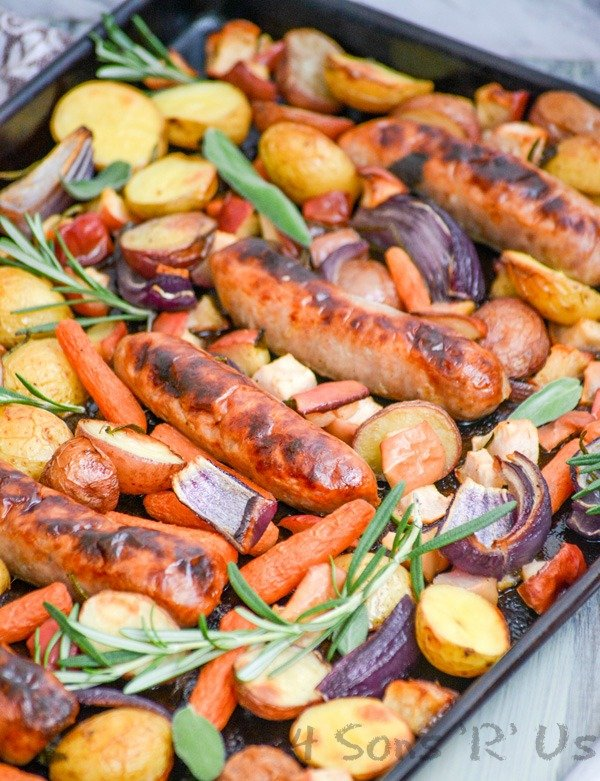 Sausage, Apple, And Herb Sheet Pan Supper shown on a dark sheet pan on a green background
