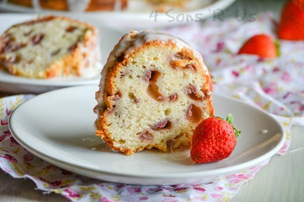 a slice of Glazed Strawberry Lemon Yogurt Cake shown on a white plate with a fresh strawberry