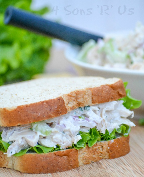lemon tarragon chopped chicken salad shown between two fluffy pieces of bread with leaf lettuce to make a sandwich