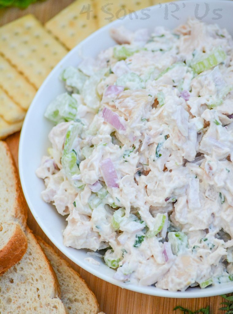 lemon tarragon chopped chicken salad served in a white bowl on a wooden cutting board
