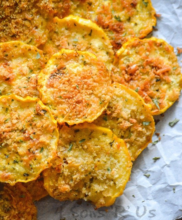 crispy yellow squash chips piled on white parchment paper sprinkled with dried herbs