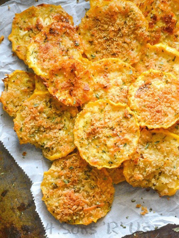Crispy Garlic Parmesan Squash Chips piled on a piece of white parchment paper sprinkled with dried herbs
