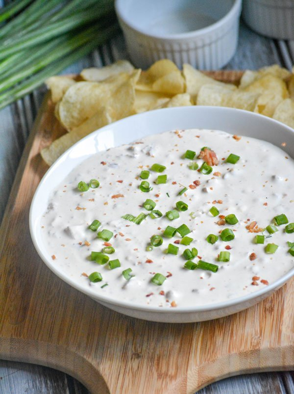 Creamy Bacon Horseradish Dip shown in a white bowl garnished with sliced green onion, and served on a wooden cutting board with crisp potato chips