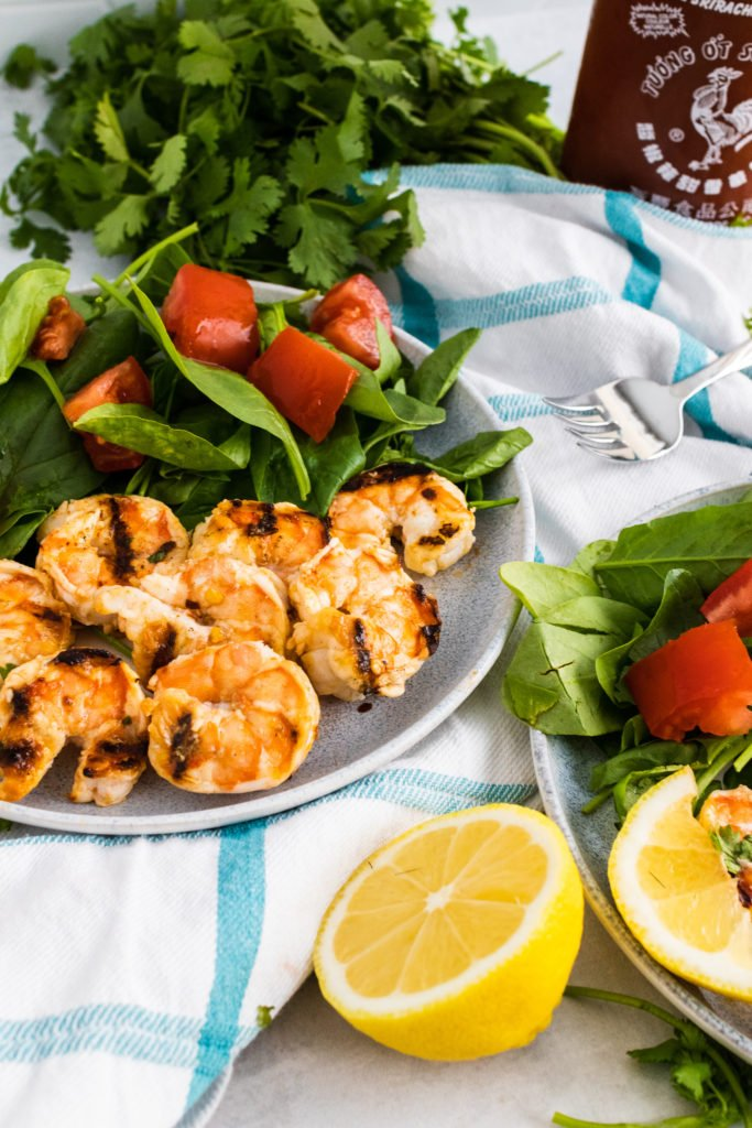 nam prik shrimp skewers shown on a plate with fresh salad on the side