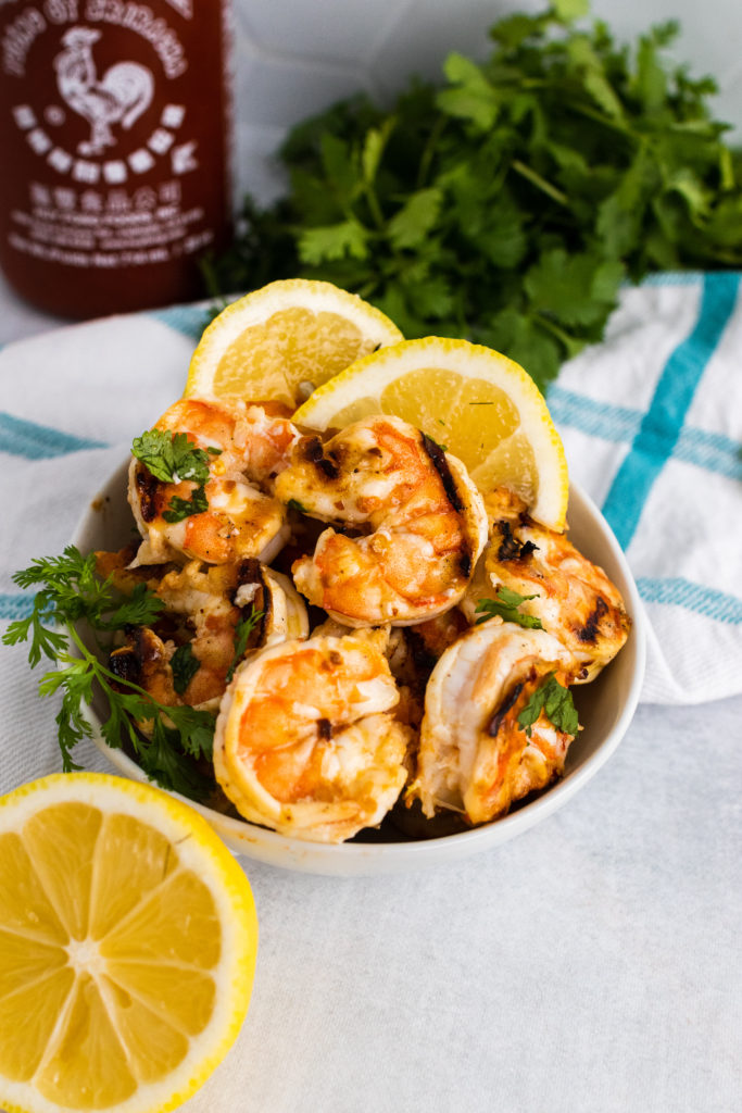 grilled nam prik shrimp pulled off their skewers and served in a white bowl with leafy garnish and fresh lemon slices