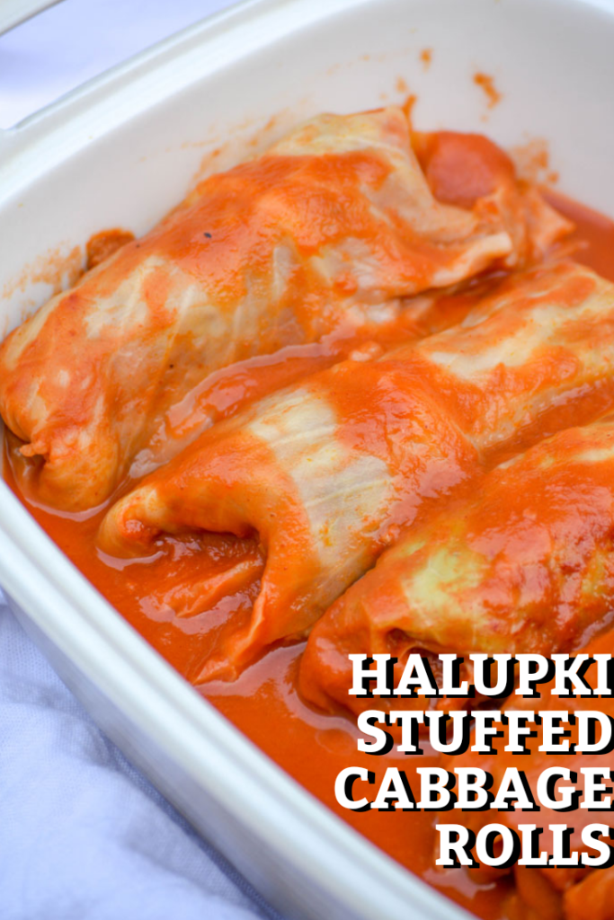 halupki stuffed cabbage rolls shown bathed in sauce in a deep casserole dish with the title of the dish overlayed in bold type