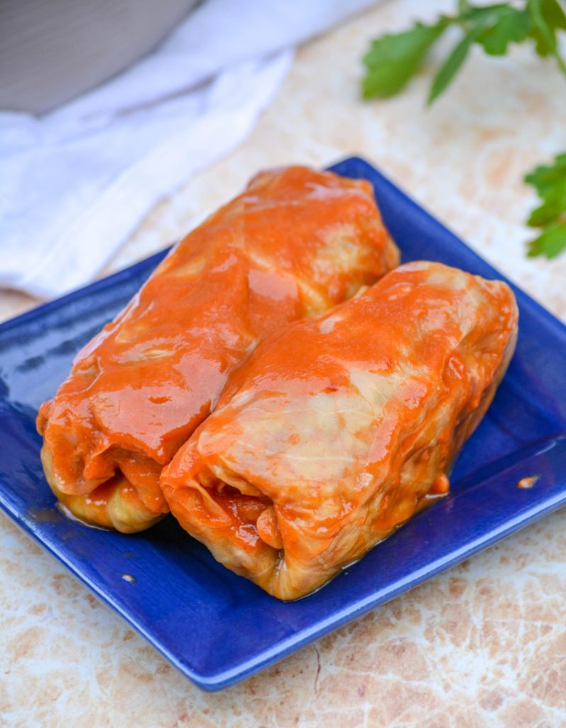 saucy Halupki Stuffed Cabbage Rolls serve on a blue square plate with a sprig of parsley and a silver serving spatula in the background