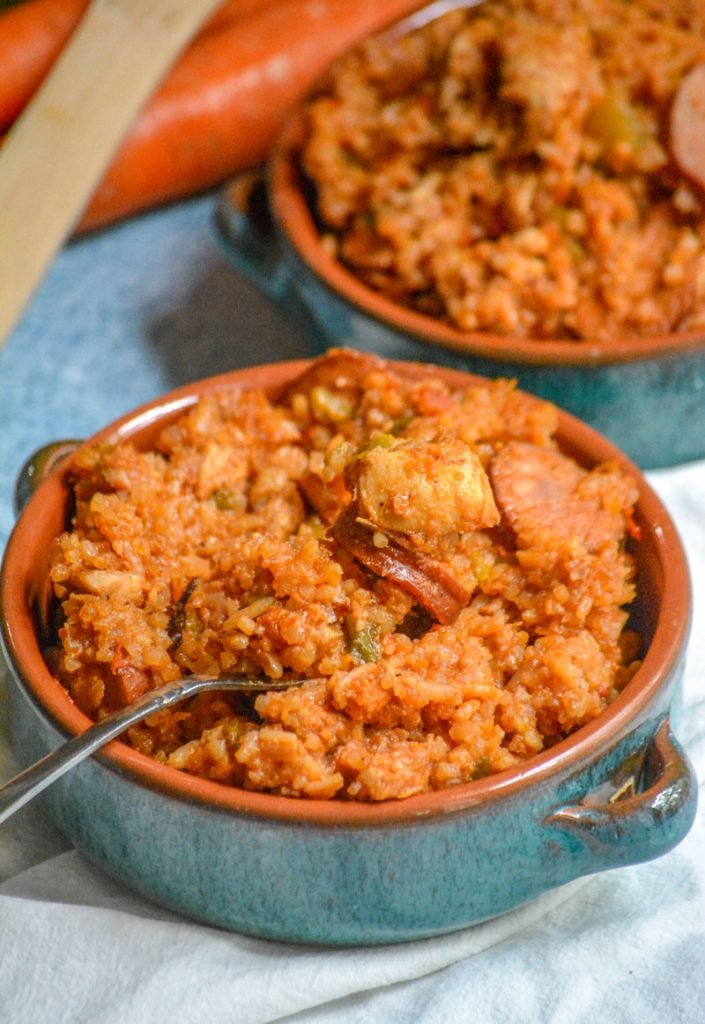 Dutch Oven Jambalaya with chicken and smoked sausage served in blue glazed terra cotta bowls