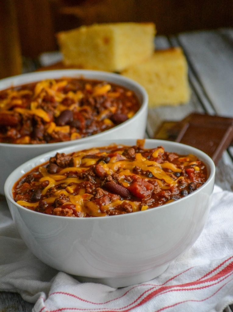 Dad's Award Winning Secret Ingredient Chili served in white bowls, topped with cheddar cheese, and sliced corn bread in the background