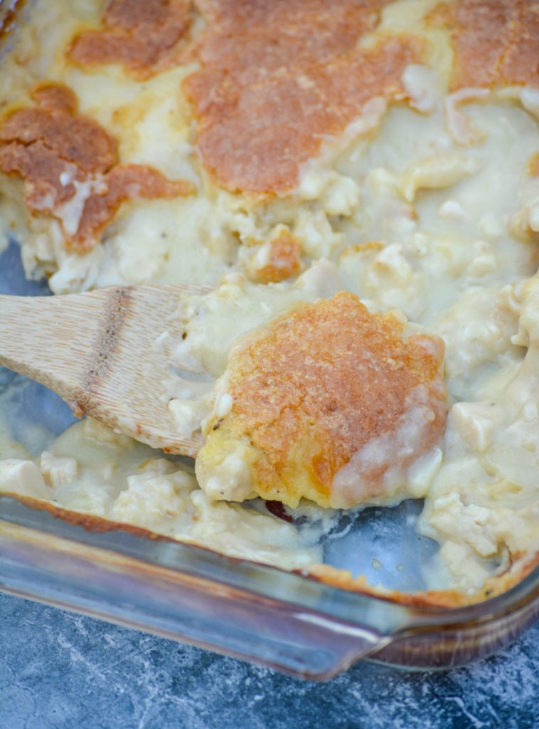 creamy Chicken & Dumping Casserole being scooped up by a wooden spoon from a clear pyrex casserole dish