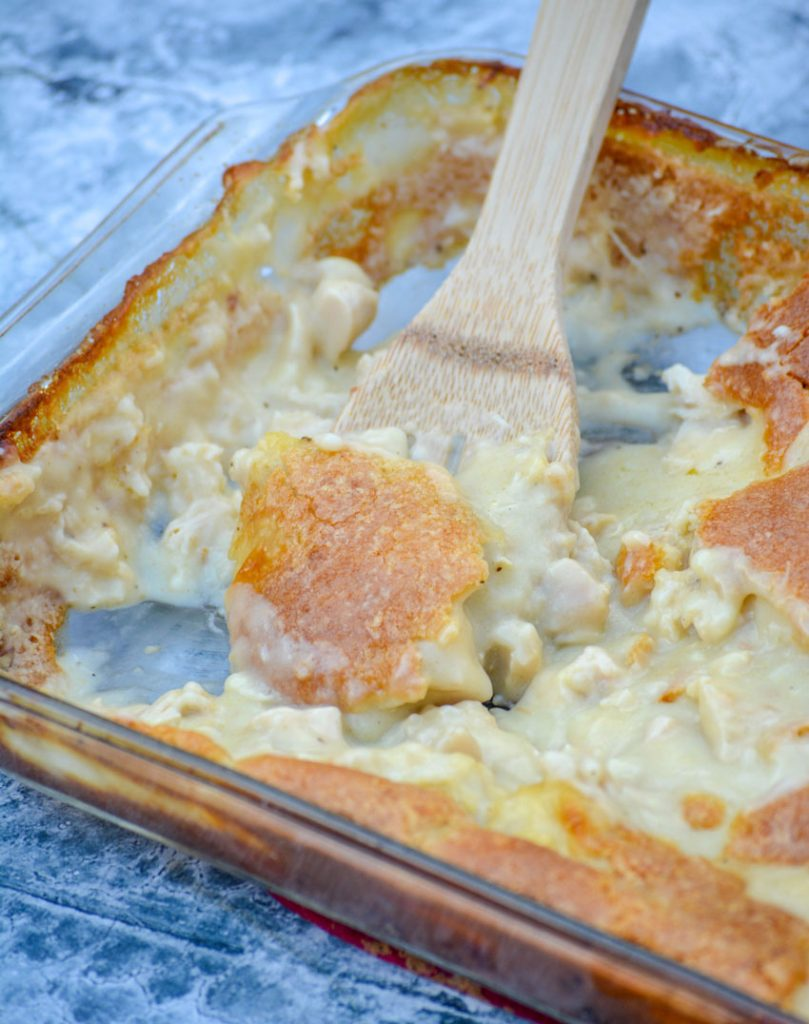 a wooden spoon shown scooping creamy chicken & dumplings casserole out of a 9x13 inch baking dish