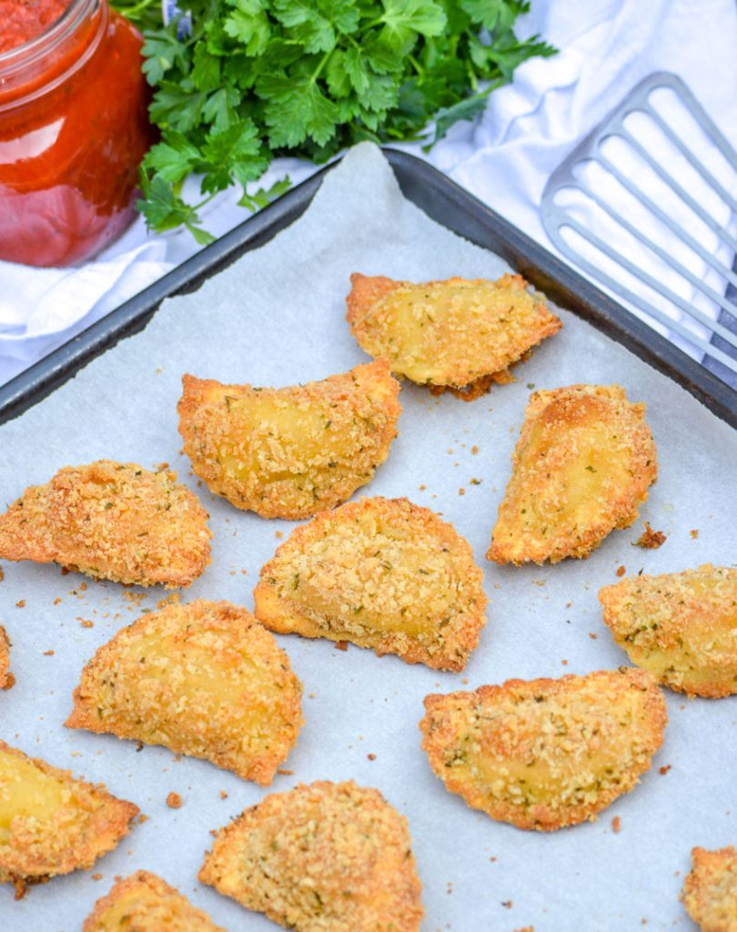 Oven Baked Toasted Ravioli shown on a parchment covered baking sheet
