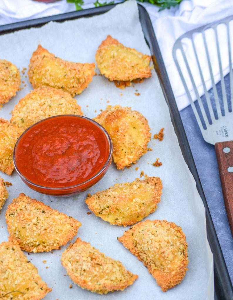 Oven Baked Toasted Ravioli on a parchment covered baking sheet with a bowl of marinara sauce