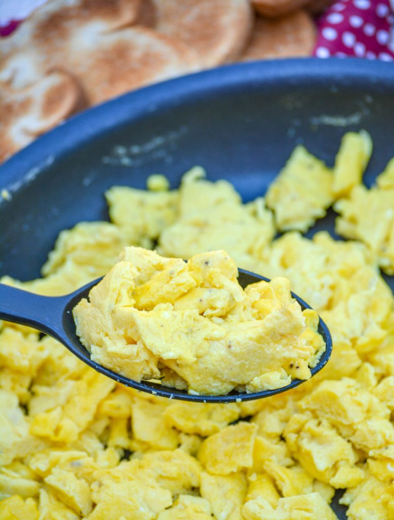 quick & easy scrambled eggs in a non stick skillet, a generous scoop is lifted into the air on a black serving spoon