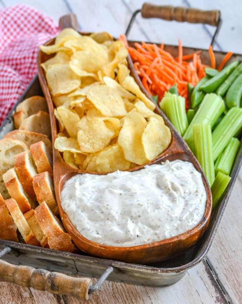 Montreal Steak Seasoning Dip served in a teak bowl with chips and veggies for dipping