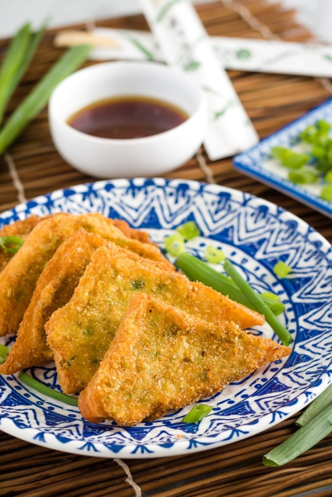 Shrimp Toast Recipe layered on a blue and white oriental style plate on a bamboo cutting board