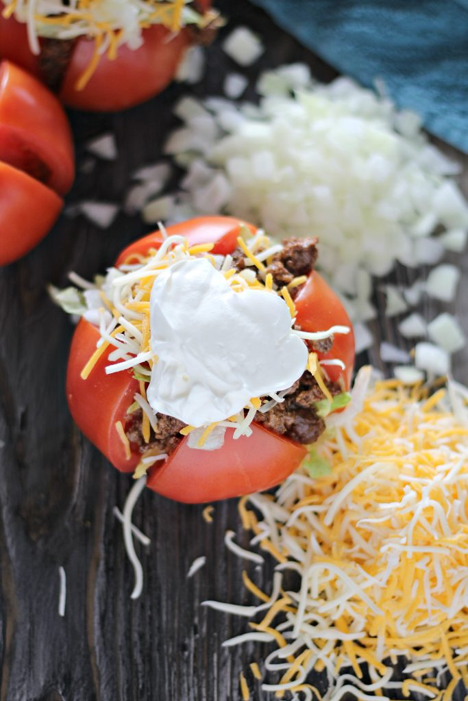 taco stuffed tomatoes topped with shredded mexican blend cheese & sour cream