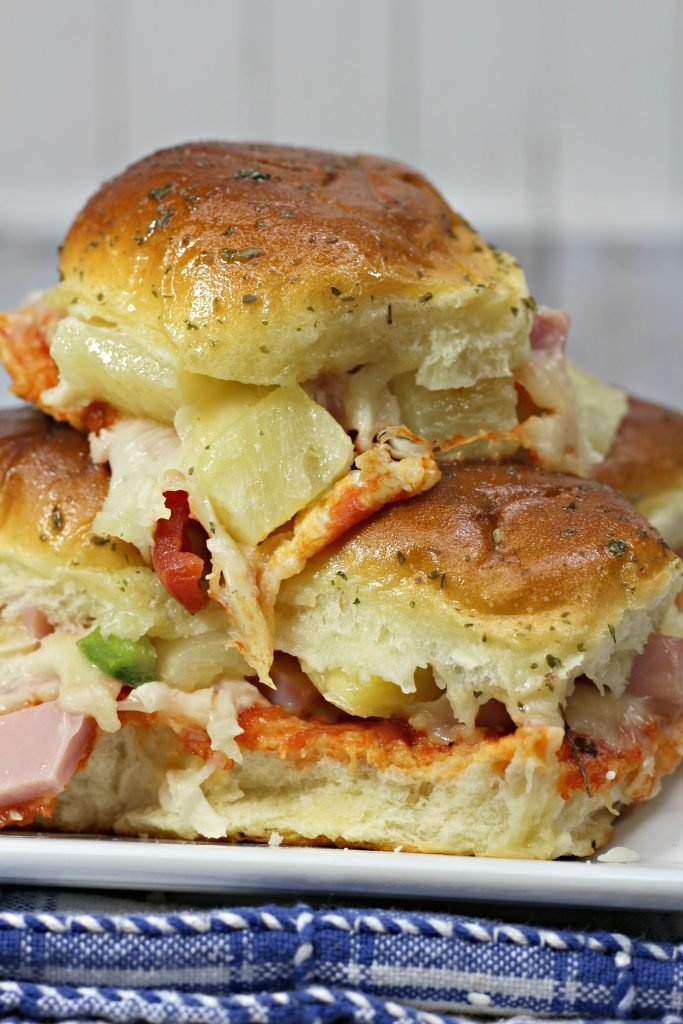 Hawaiian pizza sliders stacked up on a white plate with melted cheese, pineapple chunks, and chopped ham visible