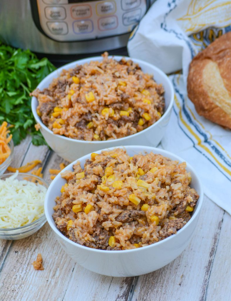 Instant Pot Cheesy Ground Beef & Rice in two white bowls with a browned loaf of crusty bread, an Instant Pot, and bright green Italian parsley in the background