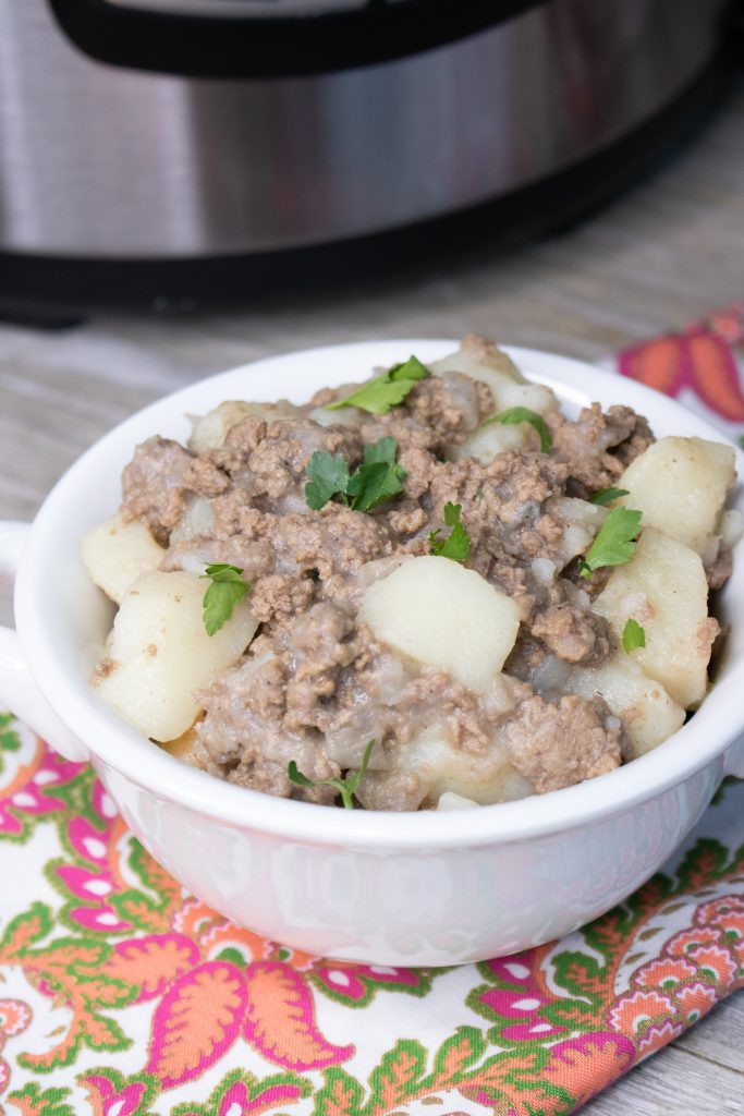 Instant Pot Ground Beef & Potato Hash in a white bowl set in front of an Instant Pot sprinkled with chopped parsley leaves
