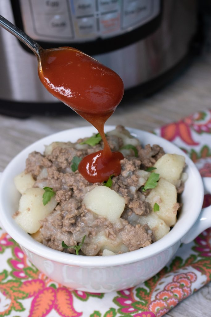 Instant Pot Ground Beef & Potato Hash topped with a spoonful of rich, red tomato ketchup