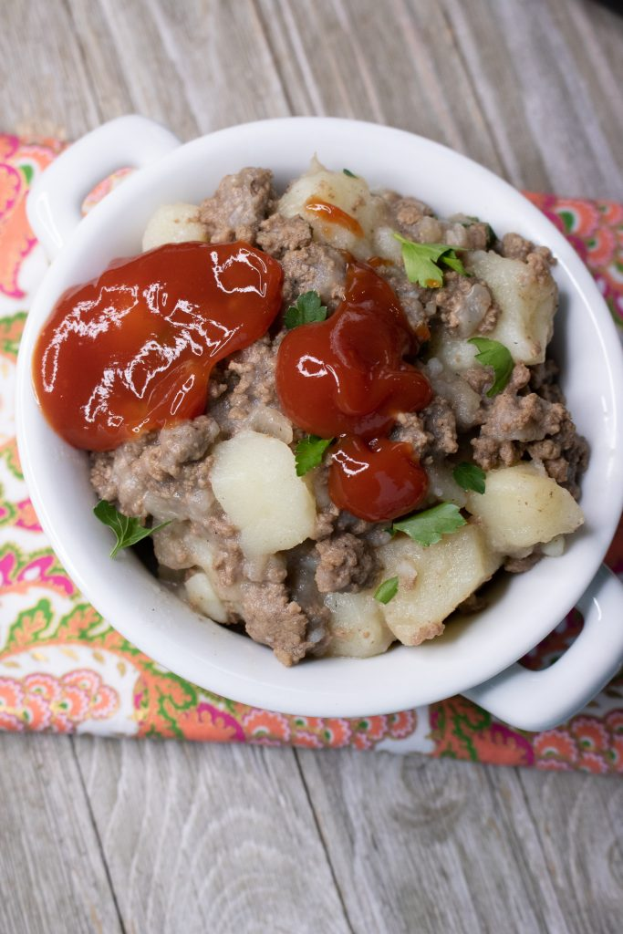 Instant Pot Ground Beef & Potato Hash served in a bright white bowl, topped with a dollop of bright tomato ketchup