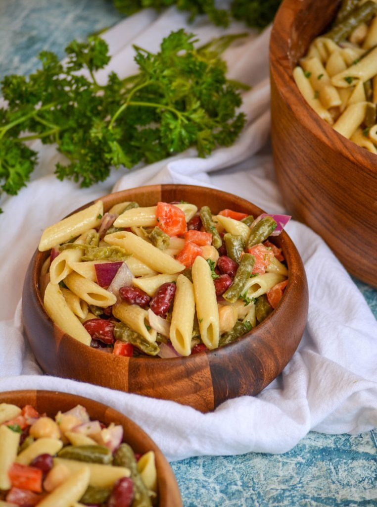 Three Bean Salad Pasta in a wooden bowl set on a white cloth with a bunch of fresh parsley in the background
