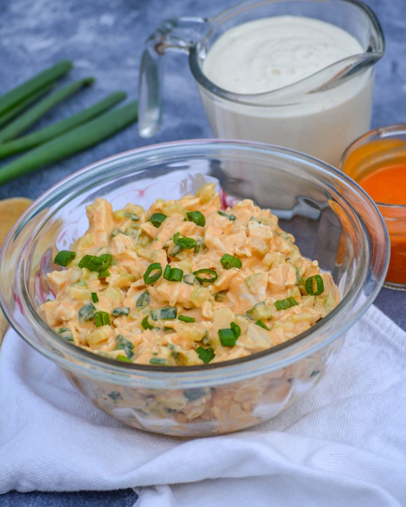 buffalo ranch chicken salad in a glass bowl topped with thinly sliced green onions