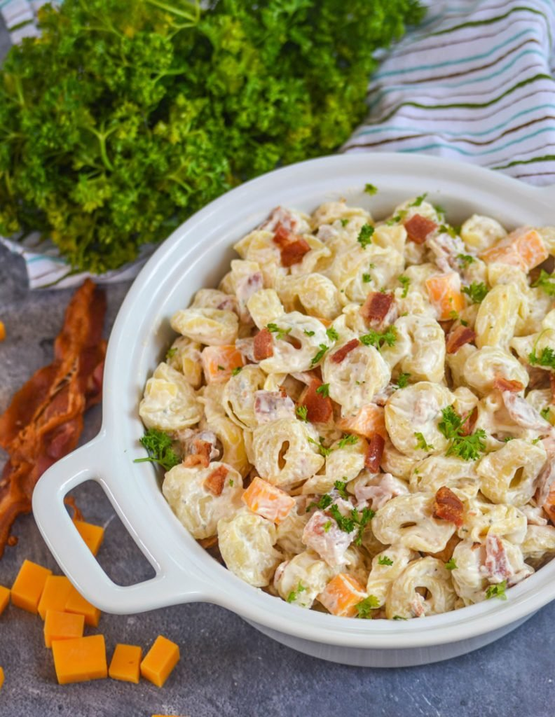 cold tortellini salad with ranch dressing in a white serving bowl on a black marbled counter with crisp slices of bacon and fresh parsley in the background