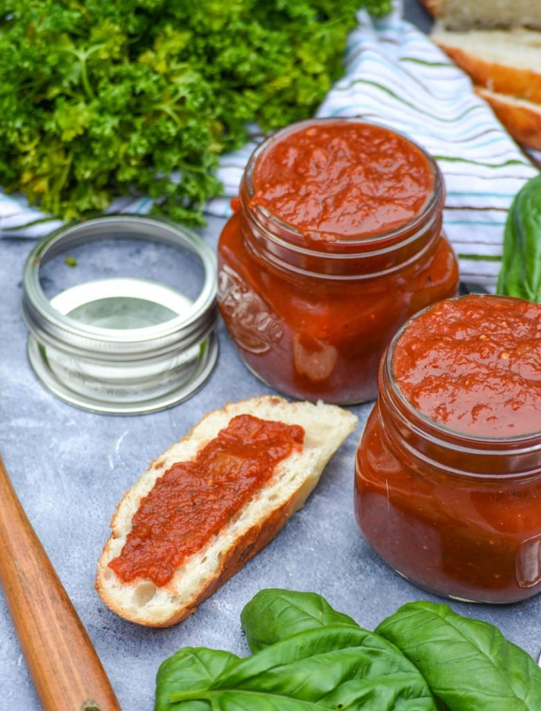 homemade marinara sauce in two glass jars with fresh parsley & basil leaves in the background. A slice of bread is also shown with a spread of marinara sauce.