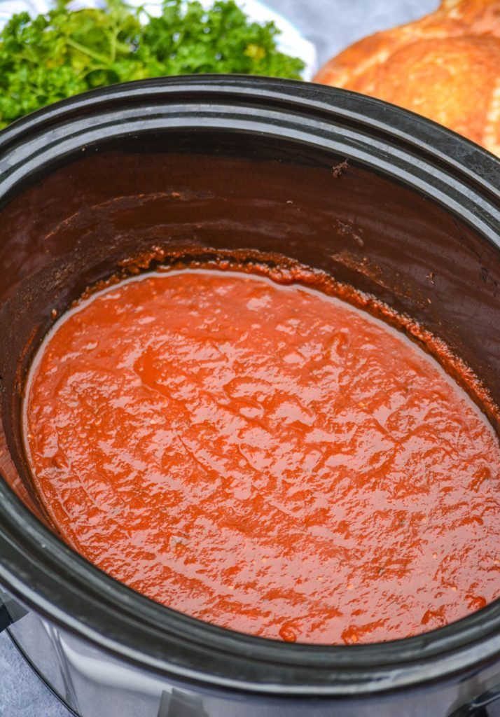 freshly made marinara sauce in the black crock of a slow cooker with parsley and bread in the background