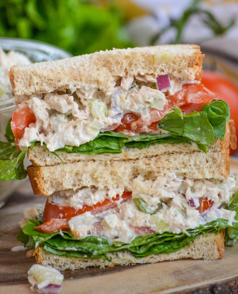 creamy dill pickle tuna salad is shown as a hearty sandwich cut in half, stacked, and studded with pickle chunks and bright red onion
