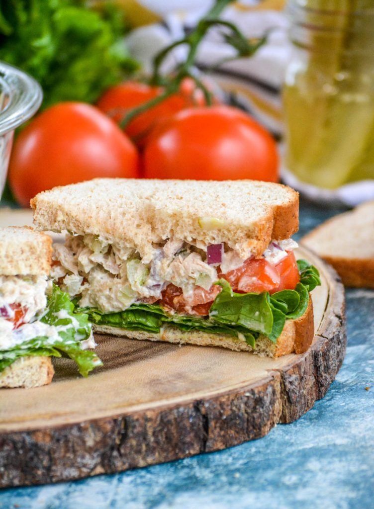 dill pickle tuna salad sandwich cut in half is shown with crisp lettuce and juicy tomato slices