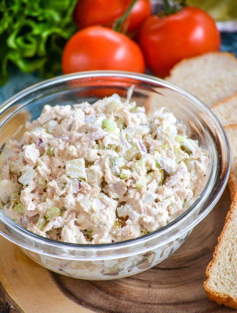 Rich & creamy, dill pickle tuna salad is in a glass bowl on a brown cutting board with freshly sliced bread green leaf lettuce and vine ripened tomatoes in the background