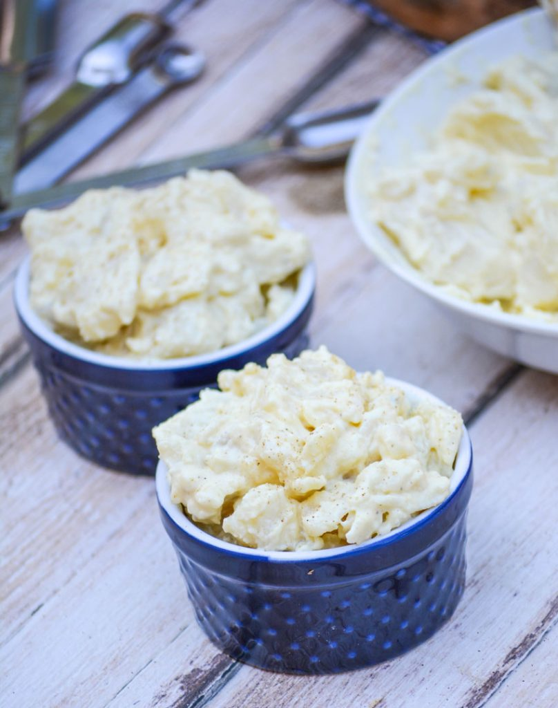 Grandma's Simple Southern Potato Salad is shown in navy blue ramekins with measuring spoons in the background on a picnic table