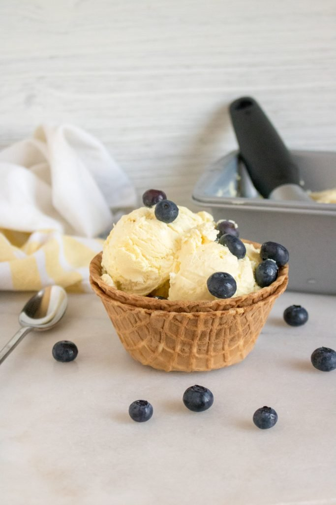 homemade no churn lemonade ice cream scoops sit in a waffle cone bowl set inside another waffle cone bowl with fresh ripe blueberries sprinkled on top