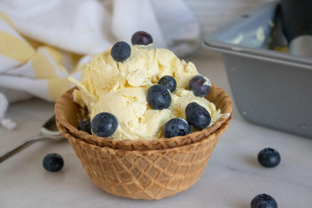 fresh blueberries top several scoops of bright yellow creamy homemade lemonade ice cream