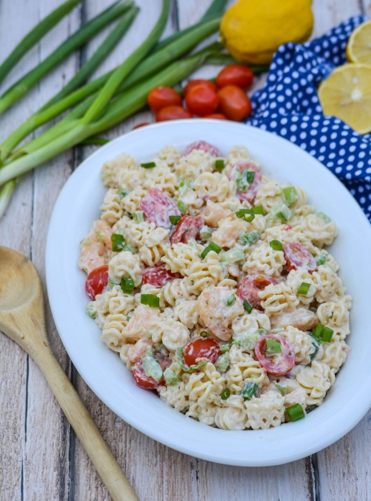 a creamy seafood style pasta salad in an oval shaped white bowl, surrounded bright fresh veggies on a picnic table with a weathered wooden spoon for serving