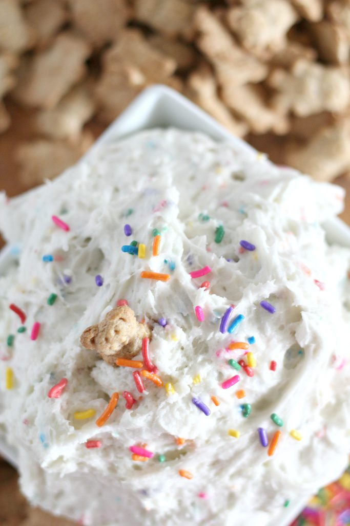 a fluffy white cake batter dip is flecked with rainbow sprinkles and piled high in a white square bowl with teddy grahams spread out in the background