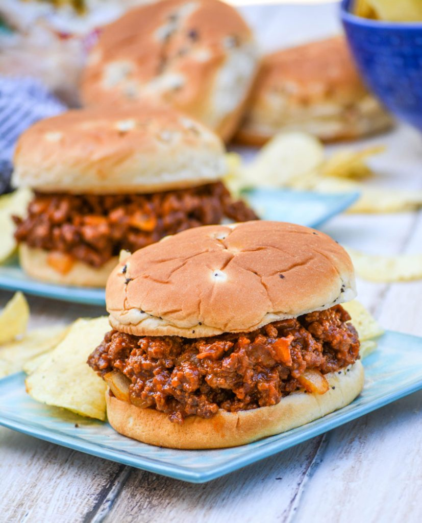 Grandma's sloppy joe's from scratch served on light blue plates with potato chips