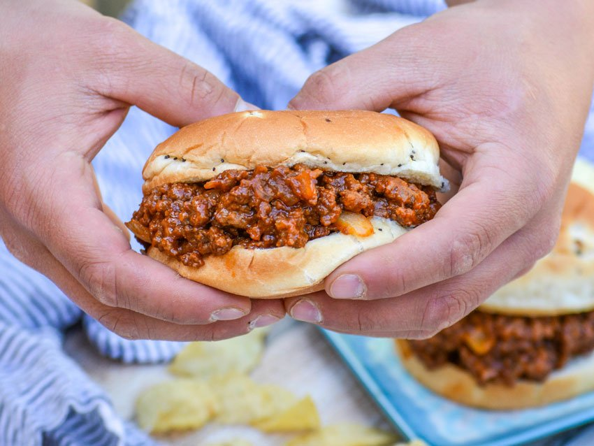 hands holding up one of Grandma's from scratch sloppy joe sandwiches