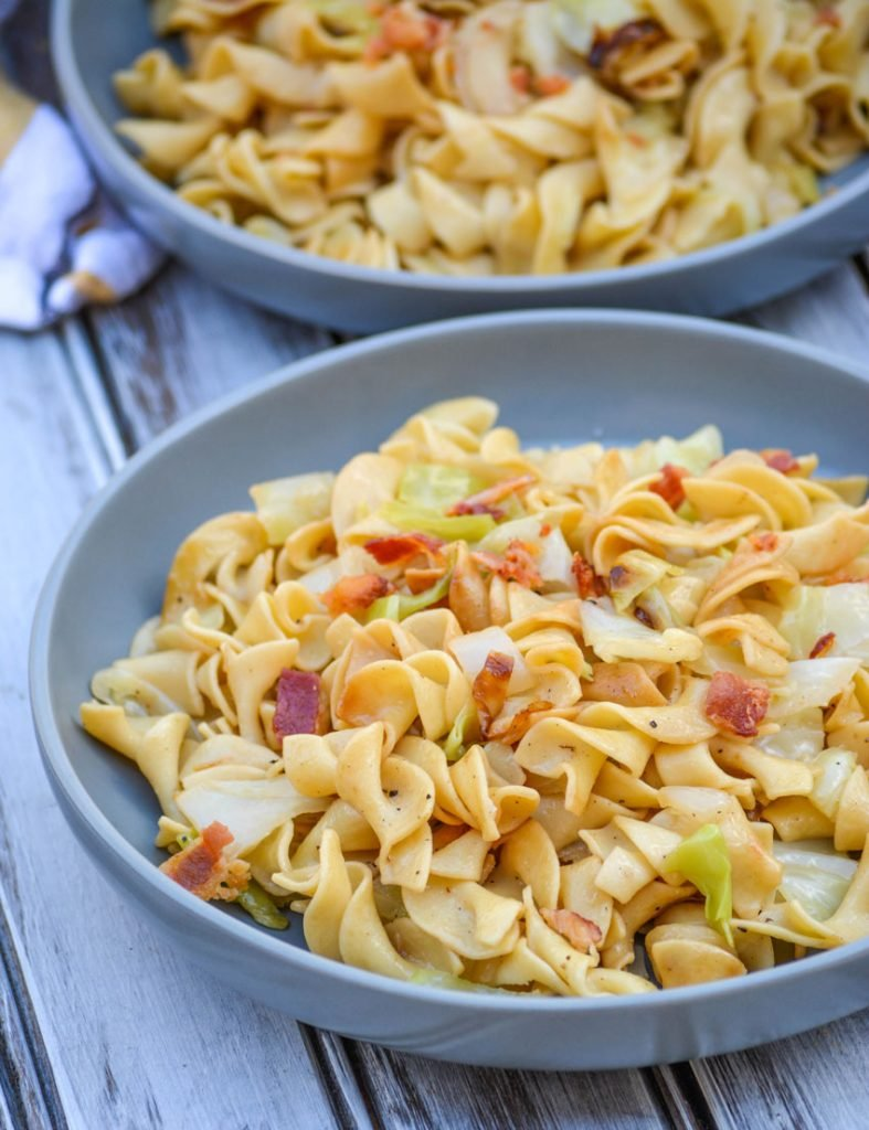 Haluski Recipe (Polish fried cabbage & noodles) topped with crisp, crumbled bacon and served on a large gray plate