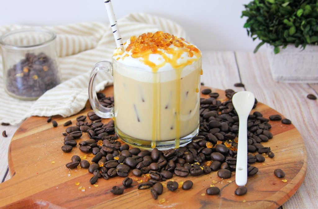 Cold Creme Brulee Coffee with Caramel in a glass mug surrounded by coffee beans on a brown cutting board. The creamy coffee's topped with whipped cream with crunchy caramel bits and a drizzle of caramel sauce. A straw sticks out from the mug and there's a white spoon on the cutting board