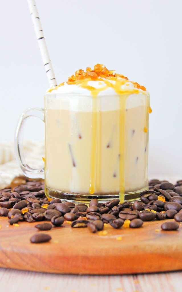Cold Creme Brulee Coffee with Caramel in a glass mug surrounded by coffee beans on a brown cutting board. The creamy coffee's topped with whipped cream with crunchy caramel bits and a drizzle of caramel sauce. A straw sticks out from the mug