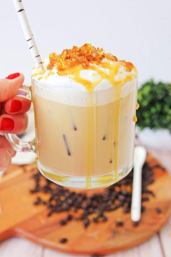 creme brulee coffee in a glass mug is held aloft the a close up view