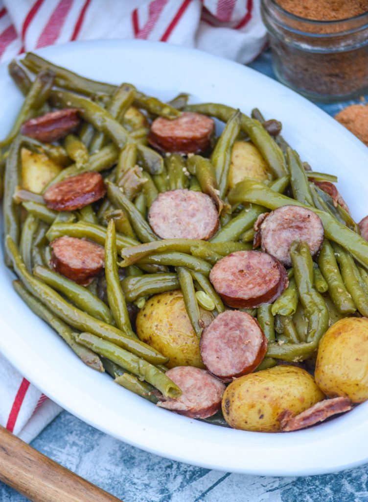 green beans, whole little potatoes, and thinly sliced smoked sausage in an oval shaped white serving bowl with a jar of Cajun seasoning and a red and white striped dish towel in the background