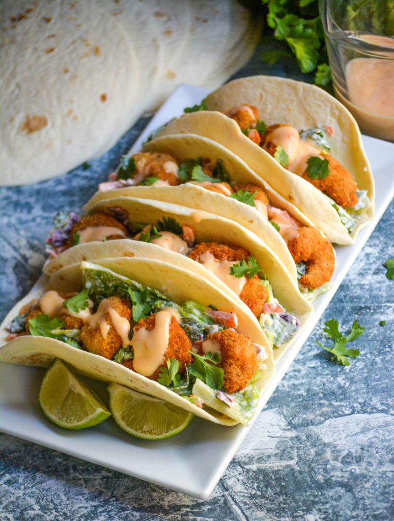 bang bang shrimp tacos lined up on a rectangular white serving platter on a blue background with extra sauce, a bunch of fresh cilantro, and flour tortillas in the background